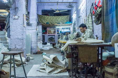 after hours: JODHPUR, INDIA - 10 FEBRUARY 2015: Tailor at work in textile factory after working hours.