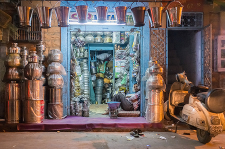closing time: JODHPUR, INDIA - 10 FEBRUARY 2015: Worker sits and rests before closing time. Stores with kitchen pottery and other products made from metal are common on Asian markets.