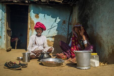 gujarat: GODWAR REGION, INDIA - 13 FEBRUARY 2015: Rabari tribeswoman in sari decorated with traditional upper-arm bracelets and jewerelly sits next to husband. Rabari are an Indian community from Gujarat.