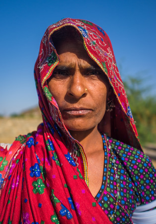 nosering: GODWAR REGION, INDIA - 14 FEBRUARY 2015: Rabari tribeswoman stands in field wearing saree and upper-arm bracelets. Rabari are an Indian community in the state of Gujarat.