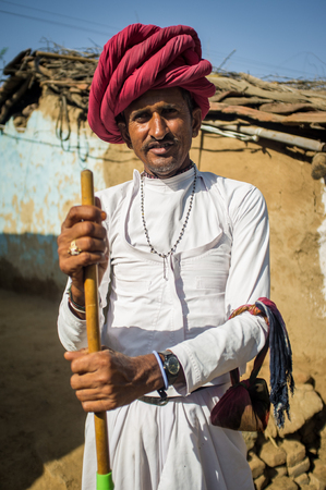 gujarat: GODWAR REGION, INDIA - 13 FEBRUARY 2015: Rabari tribesman stands in courtyard of home wearing traditional clothes and holds herding stick. Rabari or Rewari are an Indian community in the state of Gujarat.