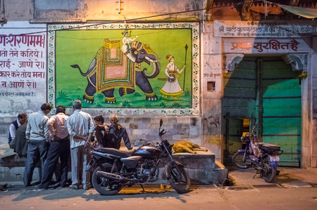 decorated bike: JODHPUR, INDIA - 16 FEBRUARY 2015: Elderly Indian men play cards on street while dog sleeps and motorbikes parked by.