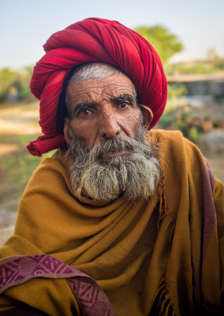 sholders: GODWAR REGION, INDIA - 14 FEBRUARY 2015: Elderly Rabari tribesman with red turban and blanket around the shoulders. Rabari or Rewari are an Indian community in the state of Gujarat.