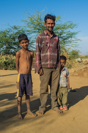 poor children: GODWAR, INDIA - 12 FEBRUARY 2015: Father and two sons stand on dusty ground in a small village. Godwar or Gorwar is a southwest region of Rajasthan state. Editorial