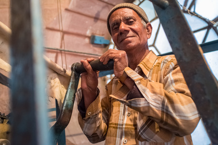 the stands: JODHPUR, INDIA - 11 FEBRUARY 2015: Ghanta Ghar clock man stands next to clock mechanism inside tower.