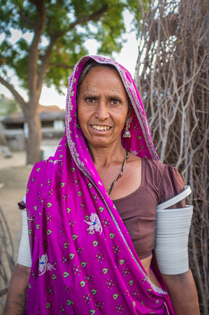 gujarat: GODWAR REGION, INDIA - 12 FEBRUARY 2015: Tribeswoman decorated with traditional tattoos on face,  jewelry and upper arm bracelets. Rabari or Rewari are an Indian community in the state of Gujarat.