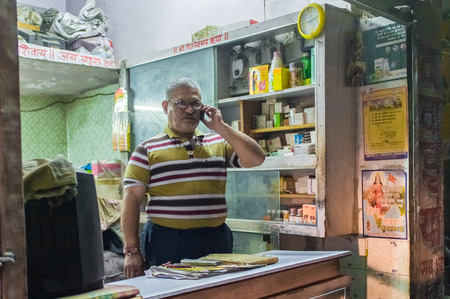 closing time: JODHPUR, INDIA - 16 FEBRUARY 2015: Local pharmacists talks on cell-phone before closing time.