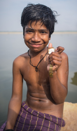 niño sin camisa: VARANASI, INDIA - 25 FEBRUARY 2015: Indian boy sits shirtless on rock in Ganges river and shows watch he found while searching through junk on river shore.