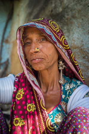 nosering: GODWAR REGION, INDIA - 13 FEBRUARY 2015: Rabari tribeswoman in sari decorated with traditional upper-arm bracelets and jewerelly. Rabari or Rewari are an Indian community from Gujarat.