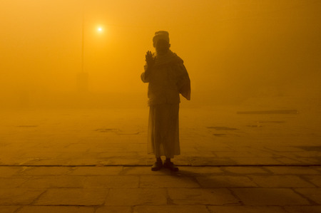 sadhu: VARANASI, INDIA - 20 FEBRUARY 2015: Pilgrim salutes on Varanasi ghat on foggy morning. Millions of pilgrims come to Varanasi every year to bath in the holy River Ganges. Editorial