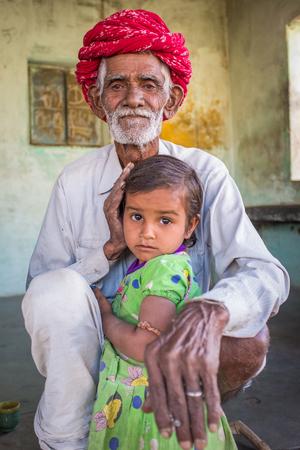 gujarat: GODWAR REGION, INDIA - 12 FEBRUARY 2015: Rabari tribesman sits and holds granddaughter. Rabari or Rewari are an Indian community in the state of Gujarat.