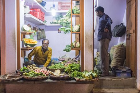 grocer: VARANASI, INDIA - 19 FEBRUARY 2015: Grocer sitting on ground with customer standing in doorway small vegetable shop on street market. Traditional traders are core part of Indian culture. Editorial