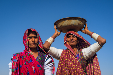 nosering: GODWAR REGION, INDIA - 14 FEBRUARY 2015: Rabari tribeswoman stands in field wearing saree and upper-arm bracelets. Balances bucket on head. Rabari are an Indian community in the state of Gujarat.