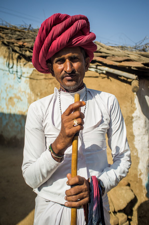 in herding: GODWAR REGION, INDIA - 13 FEBRUARY 2015: Rabari tribesman stands in courtyard of home wearing traditional clothes and holds herding stick. Rabari or Rewari are an Indian community in the state of Gujarat.