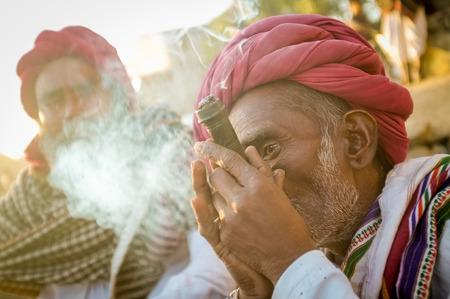 gujarat: GODWAR REGION, INDIA - 14 FEBRUARY 2015: Elderly Rabari tribesman with red turban and blanket smokes chillum. Rabari or Rewari are an Indian community in the state of Gujarat.