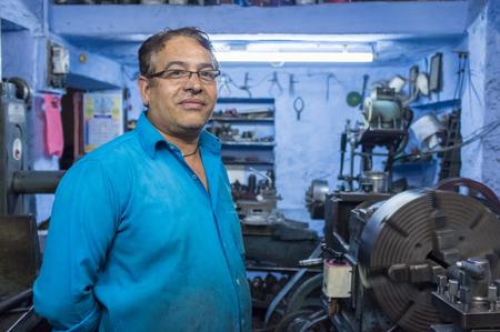 mecanico: Jodhpur, India - el 17 DE FEBRERO DE 2015: Mec�nico que trabaja tarde en el taller con equipos dispersos y maquinaria.