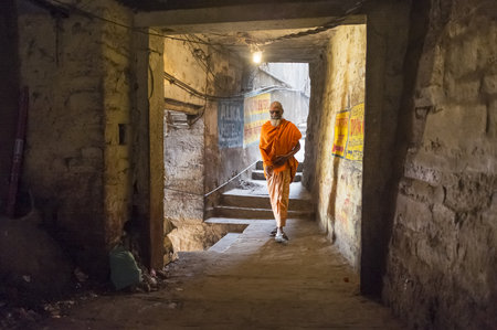 sadhu: VARANASI, INDIA - 20 FEBRUARY 2015: A sadhu walks through a passage. In Hinduism, a sadhu is a religious ascetic or holy person.