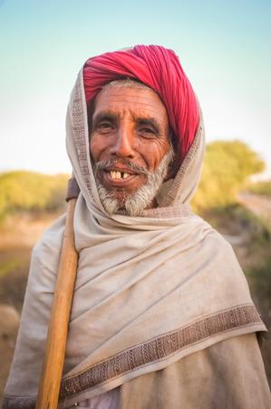 gujarat: GODWAR REGION, INDIA - 14 FEBRUARY 2015: Elderly Rabari tribesman stands with axe on sholder. Rabari or Rewari are an Indian community in the state of Gujarat. Editorial