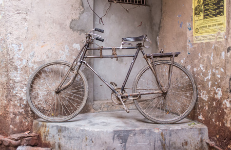 means of transportation: VARANASI, INDIA - 25 FEBRUARY 2015: Traditional Indian bicycle parked in corner of street. Bicycles are very common means of transportation on Indias streets.