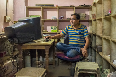 crosslegged: JODHPUR, INDIA - 16 FEBRUARY 2015: Indian man sits in office cross-legged on chair in front of computer screen.
