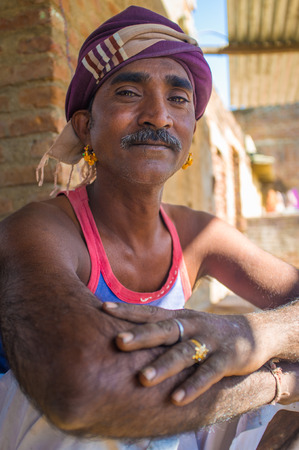sits: GODWAR REGION, INDIA - 14 FEBRUARY 2015: Mechanic with mustache wearing headscarf and big golden earings sits outside of workshop. Editorial