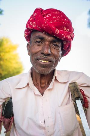 gujarat: GODWAR REGION, INDIA - 12 FEBRUARY 2015: Rabari tribesman in field with crutches. Rabari or Rewari are an Indian community in the state of Gujarat.