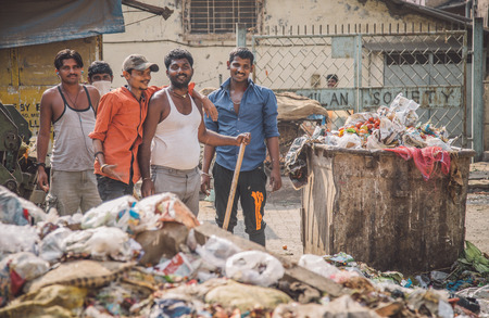 pileup: MUMBAI, INDIA - 16 JANUARY 2015: Five adult garbage men pile up garbage on slum street before throwing into garbage truck. Post-processed with grain, texture and colour effect.
