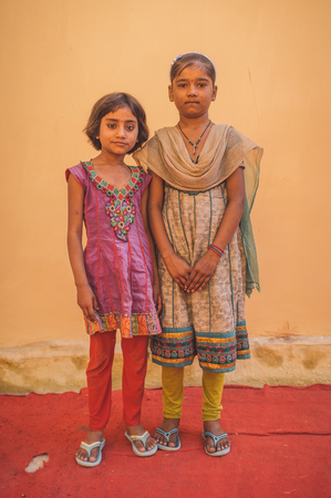 bindi: GODWAR REGION, INDIA - 15 FEBRUARY 2015: Two Indian girls pose in front of wall on red carpet. Post-processed with grain, texture and colour effect.