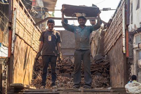 increasingly: MUMBAI, INDIA - 12 gennaio 2015: Due uomini carichi di metallo sul retro del riciclaggio camion. Dharavi baraccopoli ha una sempre pi� grande industria del riciclo.