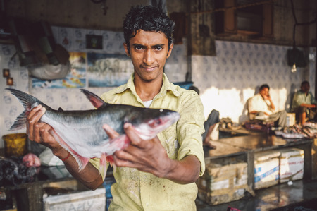 dhobi ghat: MUMBAI, INDIA - 08 JANUARY 2015: Worker on a fishmarket next to Dhobi ghat shows fish while waiting for customers. Post-processed with grain, texture and colour effect.