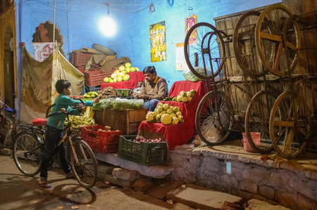 asian produce: JODHPUR, INDIA - 07 FEBRUARY 2015: Grocery store next to wooden trolleys on big wheels used for transport of goods with store owner and young boy on bicycle.