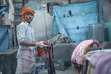 dhobi ghat: MUMBAI, INDIA - 10 JANUARY 2015: Indian worker washing a sari in Dhobi ghat. Post-processed with grain, texture and colour effect.