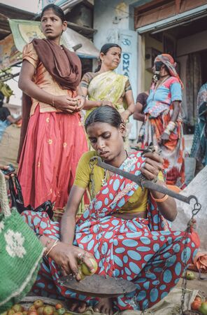 indian fair: KAMALAPURAM, INDIA - 02 FABRUARY 2015: Indian lady sells vegetables on a market close to Hampi. Post-processed with grain, texture and colour effect.