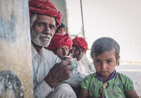 indian tribe: GODWAR REGION, INDIA - 12 FEBRUARY 2015: Rabari tribesman with other members while granddaughter stands next to him. Post-processed with grain, texture and colour effect.