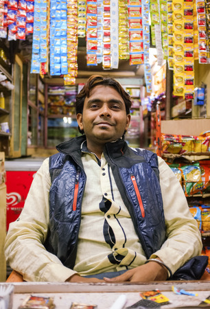 market stall: MUMBAI, INDIA - 05 FEBRUARY 2015: Portrait of Indian vendor sitting in shop with gutka hanging in background.