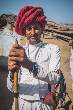 herding: GODWAR REGION, INDIA - 13 FEBRUARY 2015: Rabari tribesman stands in courtyard of home wearing traditional clothes and holds herding stick. Rabari or Rewari are an Indian community in the state of Gujarat.