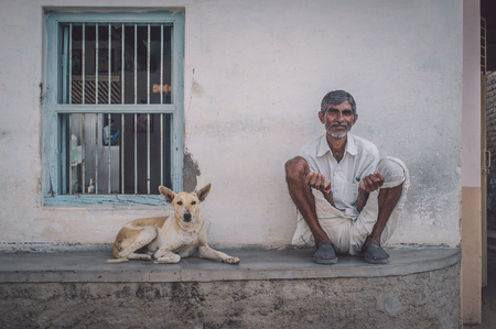 earing: GODWAR REGION, INDIA - 15 FEBRUARY 2015: Elderly Indian man and dog sit oudoors in front of home. Post-processed with grain, texture and colour effect. Editorial
