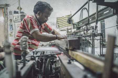 small: VARANASI, INDIA - 21 FEBRUARY 2015: Worker repairs textile machine in small factory. Post-processed with grain, texture and colour effect.
