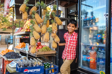 common market: HOSPET, INDIA - 04 FEBRUARY 2015: Indian boy waiting with pineapples in front of store.