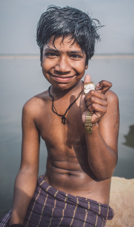 niño sin camisa: VARANASI, INDIA - 25 FEBRUARY 2015: Indian boy sits shirtless on rock in Ganges river and shows watch he found. Post-processed with grain, texture and colour effect. Editorial