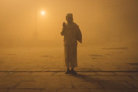 varanasi: VARANASI, INDIA - 20 FEBRUARY 2015: Pilgrim salutes on Varanasi ghat on foggy morning. Post-processed with grain, texture and colour effect. Editorial
