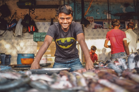 MUMBAI, INDIA - 08 JANUARY 2015: Worker on a fishmarket poses while waiting for customers. Post-processed with grain, texture and colour effect. Editorial