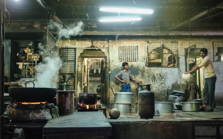 underpaid: JODHPUR, INDIA - 07 FEBRUARY 2015: Two Indian workers in candy factory. Workers around India are underpaid, overworked and unhappy. This working environment is common in India. Editorial