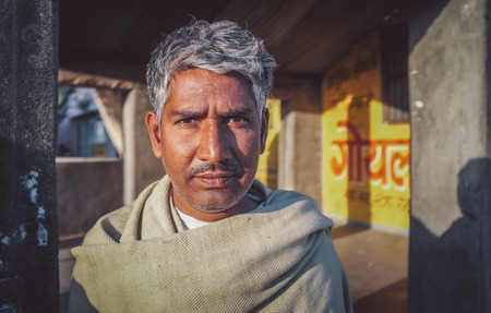 sholders: GODWAR REGION, INDIA - 14 FEBRUARY 2015: Adult Indian man with grey hair stands in street. Post-processed with grain, texture and colour effect.