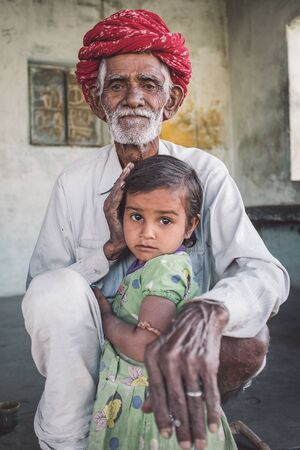 indian tribe: GODWAR REGION, INDIA - 12 FEBRUARY 2015: Rabari tribesman sits and holds granddaughter. Post-processed with grain, texture and colour effect.