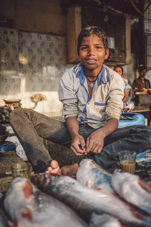 dhobi ghat: MUMBAI, INDIA - 08 JANUARY 2015: Young worker on a fishmarket next to Dhobi ghat posing while waiting for customers. Editorial