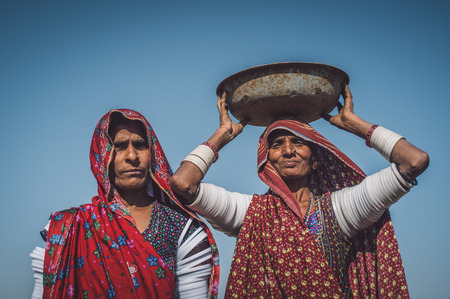 nosering: GODWAR REGION, INDIA - 14 FEBRUARY 2015: Rabari tribeswoman stands in field wearing saree and upper-arm bracelets. Balances bucket on head. Post-processed with grain, texture and colour effect.