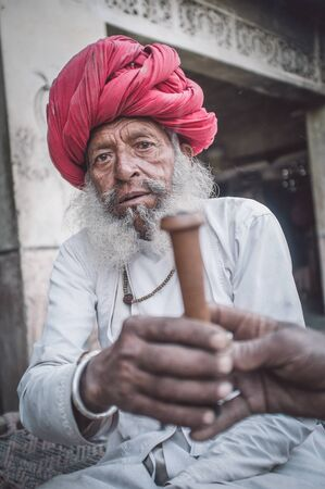 gujarat: GODWAR REGION, INDIA - 12 FEBRUARY 2015: Elderly Rabari tribesman with traditional turban, clothes and long beard hands out chillum. Rabari or Rewari are an Indian community in the state of Gujarat.