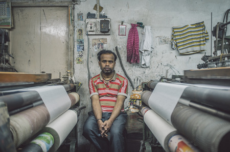 textile machine: VARANASI, INDIA - 21 FEBRUARY 2015: Worker sits on chair next to textile machine in small factory. Post-processed with grain, texture and colour effect.