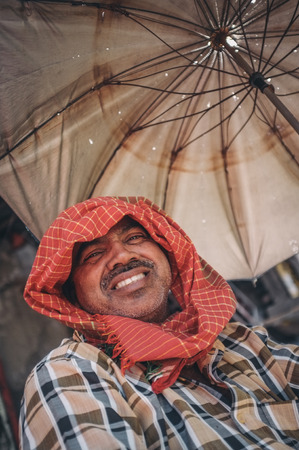 postproduction: MUMBAI, INDIA - 10 JANUARY 2015: Man sitting under a parasole. Post-processed with grain, texture and colour effect.